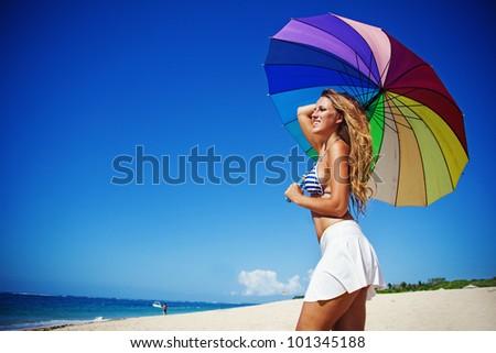 Beautiful  woman with umbrella on beach, bali - stock photo