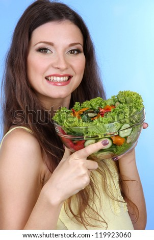 Beautiful woman with vegetable salad on blue background