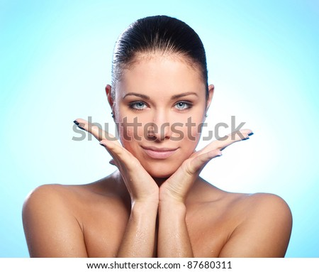 Beautiful woman with water drops on face against blue background - stock photo