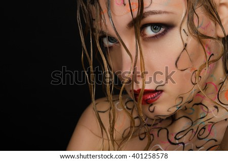 Beautiful woman with wet hair and face art on black background  - stock photo