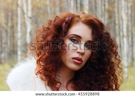 Beautiful woman with white fur poses in autumn forest, close up