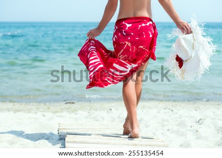 Beautiful woman with white hat walks at the sea side in red dress