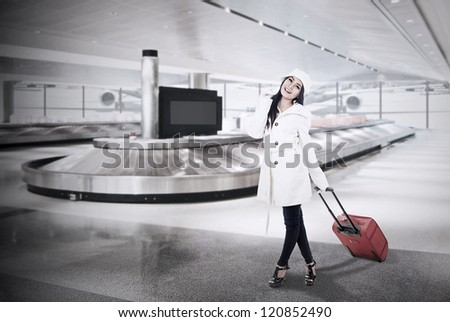 Beautiful woman with winter coat collect her luggage at airport - stock photo