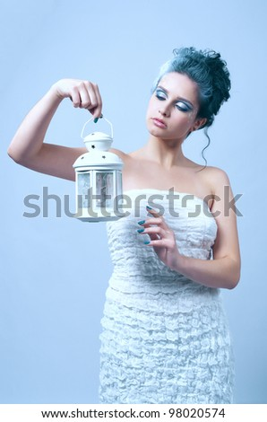 Beautiful woman with winter style makeup and lantern in hand - stock photo