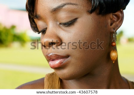 beautiful woman with wooden earrings sensually looks down outdoors