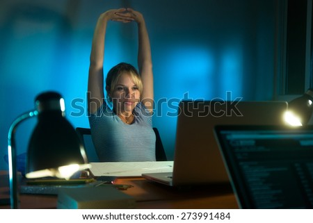 Beautiful woman working as interior designer, staying late at night in office with drawings and laptop computer to complete a project. The girl yawns and stretch her arms - stock photo
