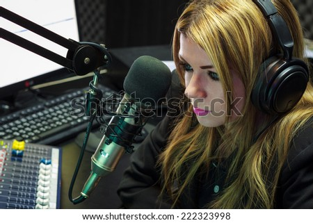 Beautiful Woman Working As Radio DJ Live In Studio - stock photo