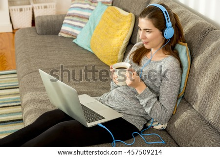 Beautiful woman working at home with a laptop while listen music and drinking coffee - stock photo