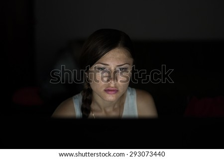 Beautiful woman working late at night in office, surfing the web and writing post on social network with computer - stock photo
