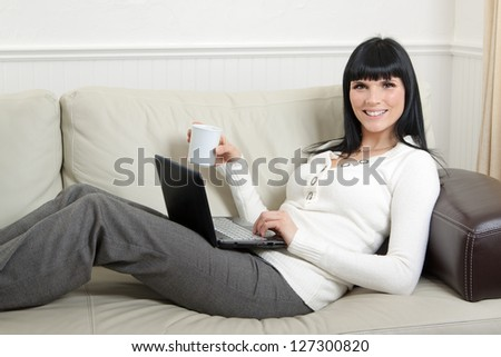 Beautiful woman working on her computer from the comfort of her home