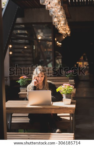 Beautiful woman working on her laptop on a stylish urban restaurant - stock photo