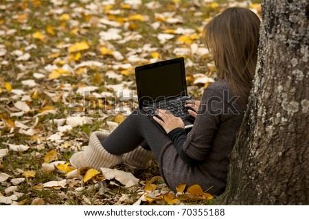 Beautiful woman working with a laptop in outdoor - stock photo