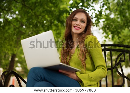 beautiful woman working with her laptop in the park