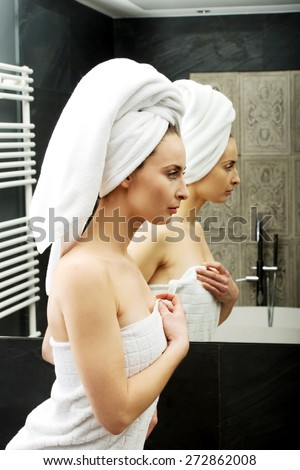 Beautiful woman wrapped in towel at bathroom. - stock photo