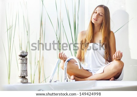 Beautiful woman wrapped with a towel  relaxing in light interior - stock photo