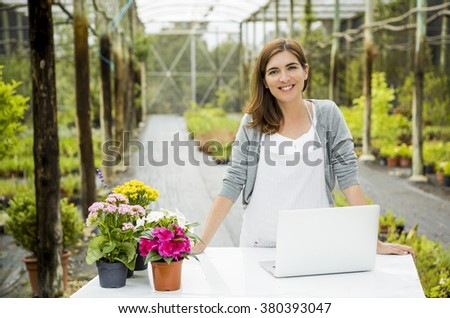 Beautiful woman wroking in a greenhouse and looking at camera while smiling