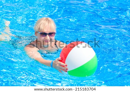 Beautiful woman 30-40 years old, learning to swim with a beach ball