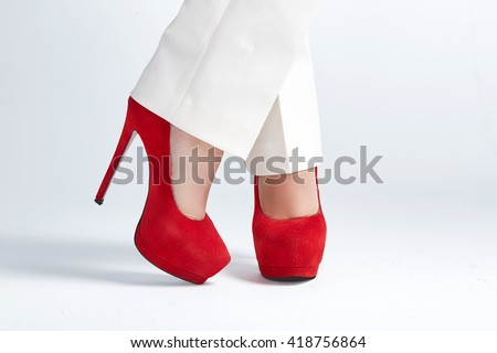 Beautiful womanish feet in red shoes standing on light background