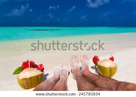 beautiful women and man legs with coconuts red flowers in Maldives  romantic  atoll island paradise luxury  resort about coral reef amazing  fresh  freedom snorkel adventure - stock photo