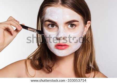 Beautiful women applying white clay facial mask on her face by brush - stock photo
