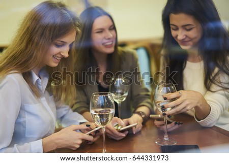 Beautiful women best friends communicating with each other with glasses of wine and telling funny stories while using modern smartphones and discussing last news at meeting in cozy cafe interior