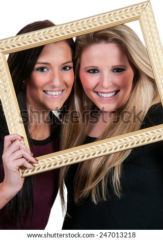 Beautiful women best friends looking through a picture frame - stock photo