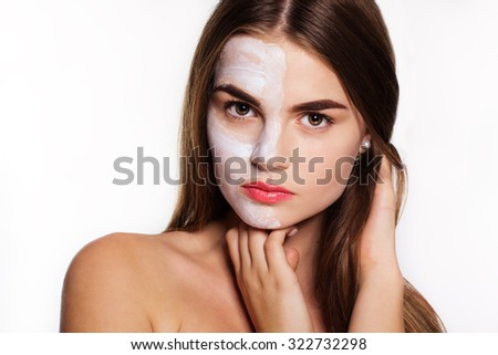 Beautiful women getting white clay facial mask on half part of face - stock photo