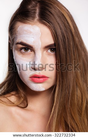 Beautiful women getting white clay facial mask on half part of face, spa concept - stock photo