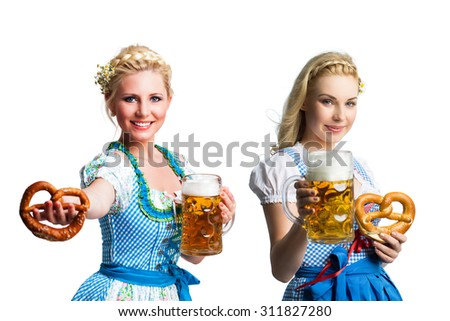 beautiful women in a traditional bavarian dirndl with beer and pretzel in front of an isolated background - stock photo