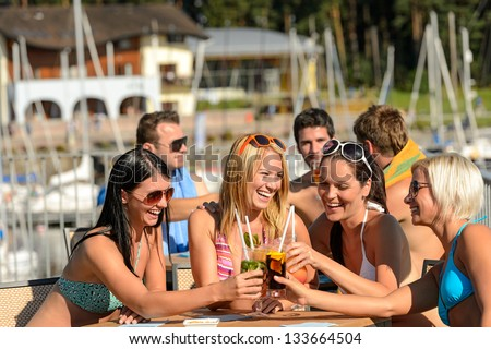 Beautiful women in bikinis toasting with cocktails at beach - stock photo
