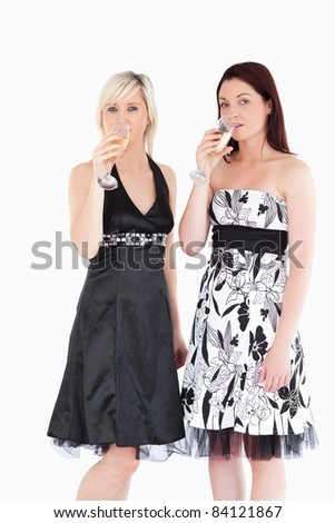 Beautiful women in dresses drinking champagne in a studio