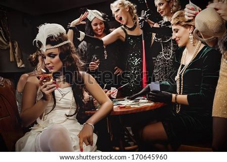 Beautiful women in evening dresses playing poker - stock photo