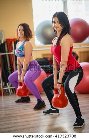 Beautiful women in gym doing exercises with dumbbells