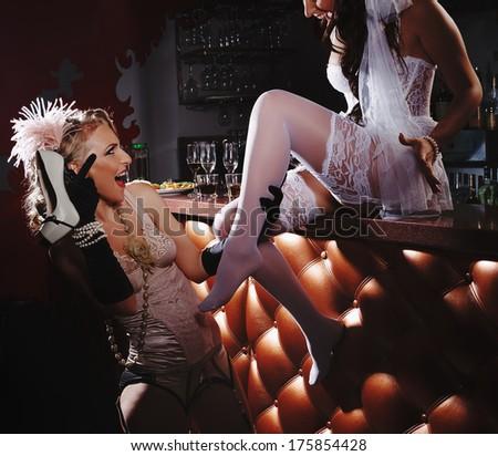 Beautiful women in retro underwear next to bar counter - stock photo