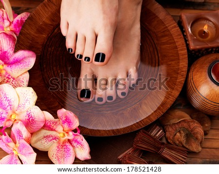 Beautiful women legs with black pedicure after Spa procedures - Spa treatment concept - stock photo