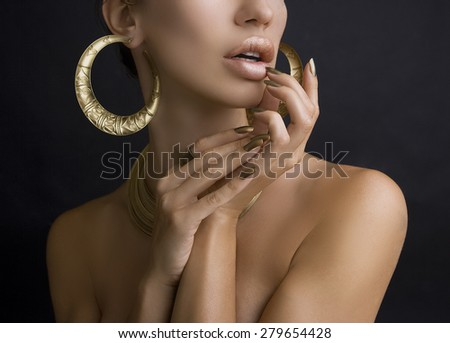 Beautiful Women Lips with Stylish Golden Shiny Lipstick and Hands with Golden Manicure and Gold Jewelery on dark background. Make-Up, Fashion, Beauty. Nail Care - stock photo