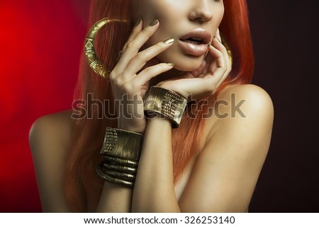 Beautiful Women Lips with Stylish Golden Shiny Lipstick and Hands with Golden Manicure and Gold Jewelery on dark background. Makeup, Fashion, Beauty. Nail Care. Redhead Sexy Women - stock photo