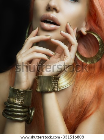 Beautiful Women Lips with Stylish Golden Shiny Lipstick and Hands with Golden Manicure and Gold Jewelery on dark background. Makeup, Fashion, Beauty. Nail Care. Redhead Sexy Women