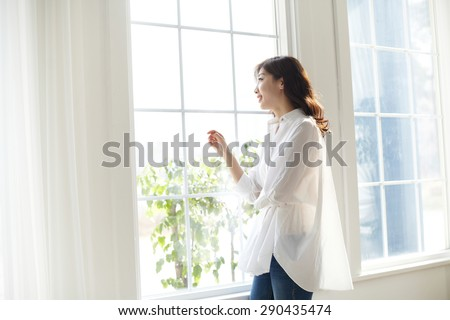 beautiful women looking out a window with a smile on their face in a bright room