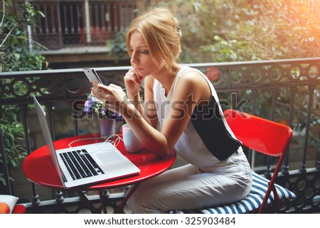 Beautiful women reading news on her cell telephone while relaxing after viewing the film on portable laptop computer, young female using mobile phone after work on net-book during recreation time  - stock photo