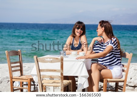 Beautiful women sitting at a seaside cafe and drinking a coffee - stock photo