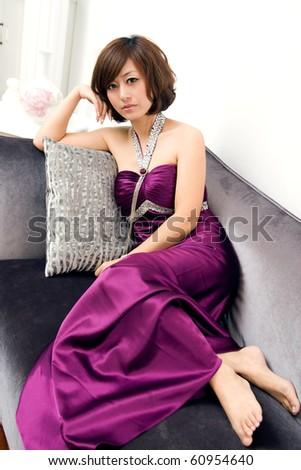 beautiful women sitting in sofa,dressing a purple evening dress - stock photo