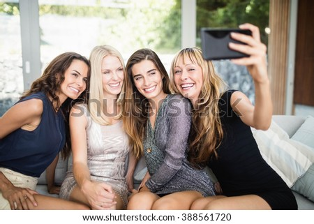 Beautiful women smiling and taking selfie with mobile phone at party - stock photo