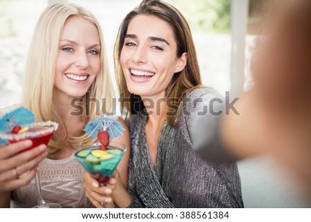 Beautiful women taking selfie with mobile phone and having mocktail