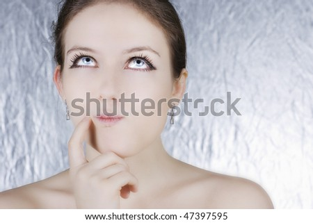 Beautiful women with a pensive expression looking up over silver background - stock photo