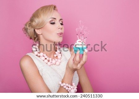 Beautiful women with cream dress holding small cake with colorful candle. Birthday, holiday. Studio portrait over pink background  - stock photo