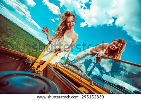 Beautiful women with tools are repairing a car on the rural road - stock photo