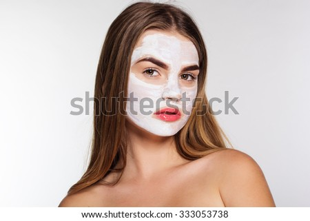 Beautiful women with white clay facial mask on her face - stock photo
