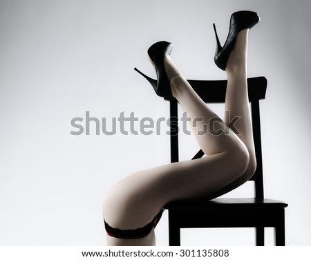 Beautiful womens legs with heels on chair, as if fallen