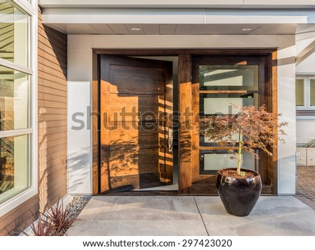 Beautiful Wood Door as Entrance to New Luxury Home: Large and Wide Hardwood Door with Windows and Potted Plant to Right of Door in Exterior of Beautiful House. Cement Patio. Door is Slightly Ajar/Open - stock photo